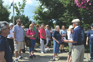 2015 Tour participants view historic photos during a tour lead by longtime ACTC professor Ernie Tucker. Photo By Mike James, The Independent